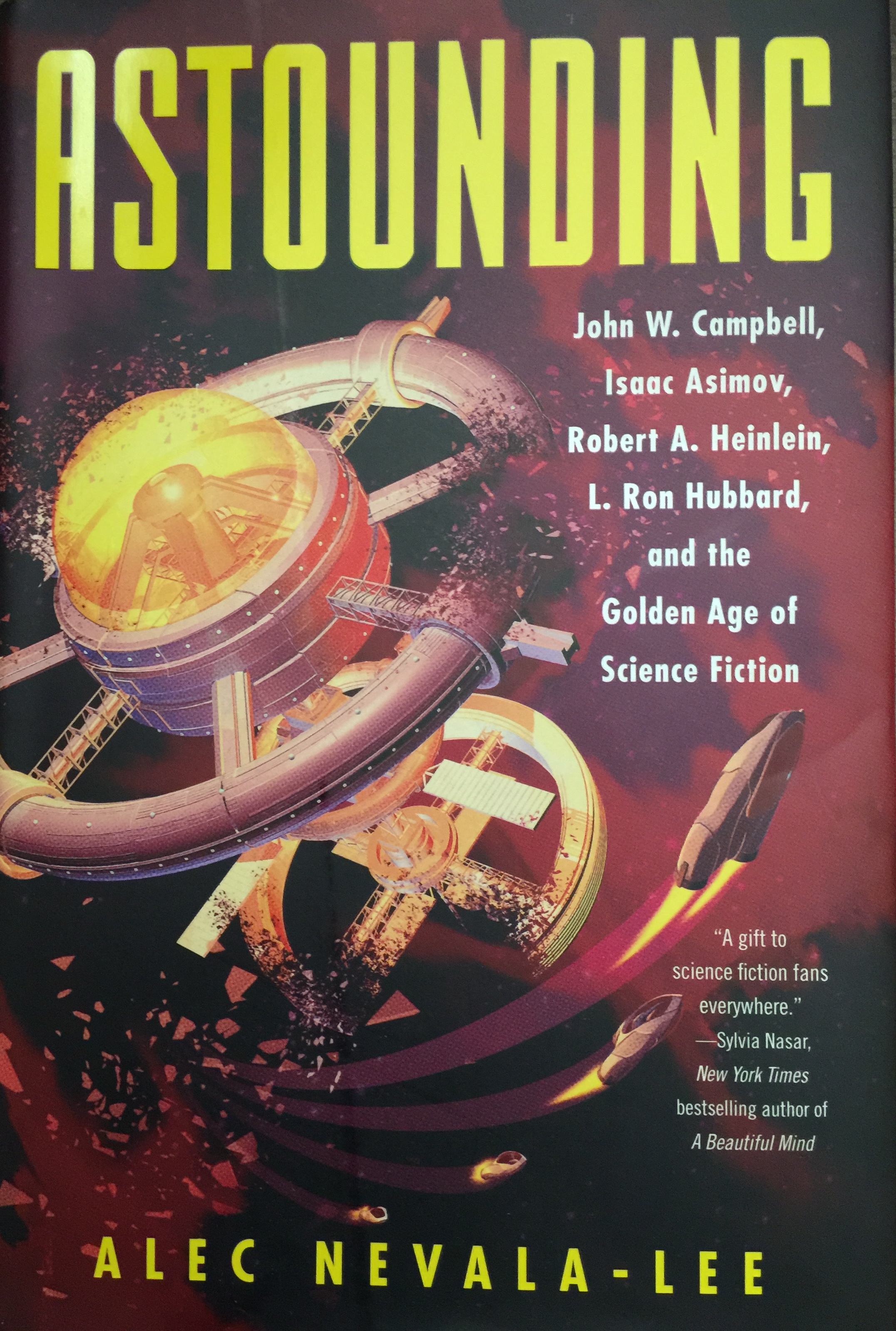 "The cover of a book titled ""Astounding."" It features a space station that looks like two wheels on an axel; some of the rings are broken and four rockets are flying away."