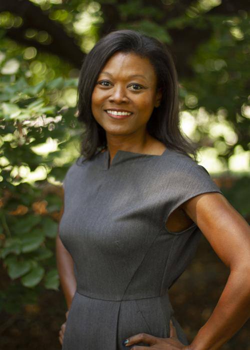 A Black woman stand in front of out-of focus greenery. She has long black hair and is wearing an inviting smile and shot-sleeved black dress.