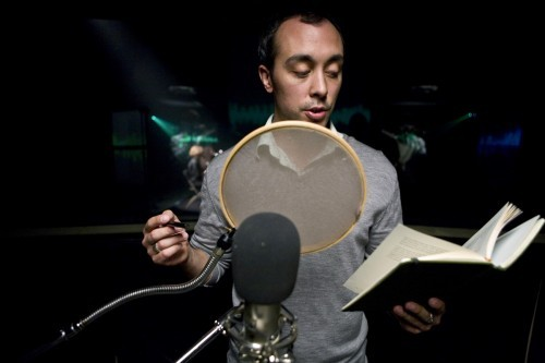 A white man with short black hair is reading aloud behind a pop filter and microphone. He is looking at a book in his left hand.