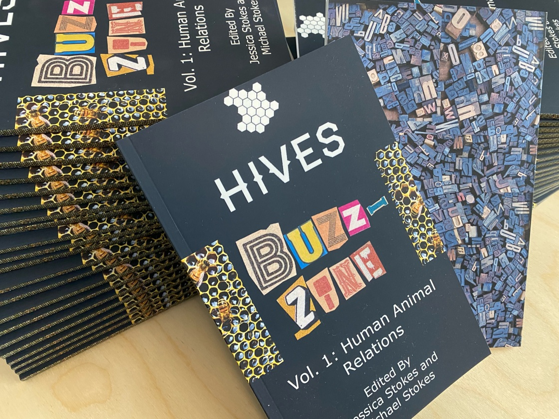 """Two stacks of magazines on their sides support two zines as they slouch into the foreground. The zines have honeycombs on their spines. The front of one zine is visible and reads """"HIVES Buzz-Zine"""" The back of the other zine shows a pile of printer's block letters."""