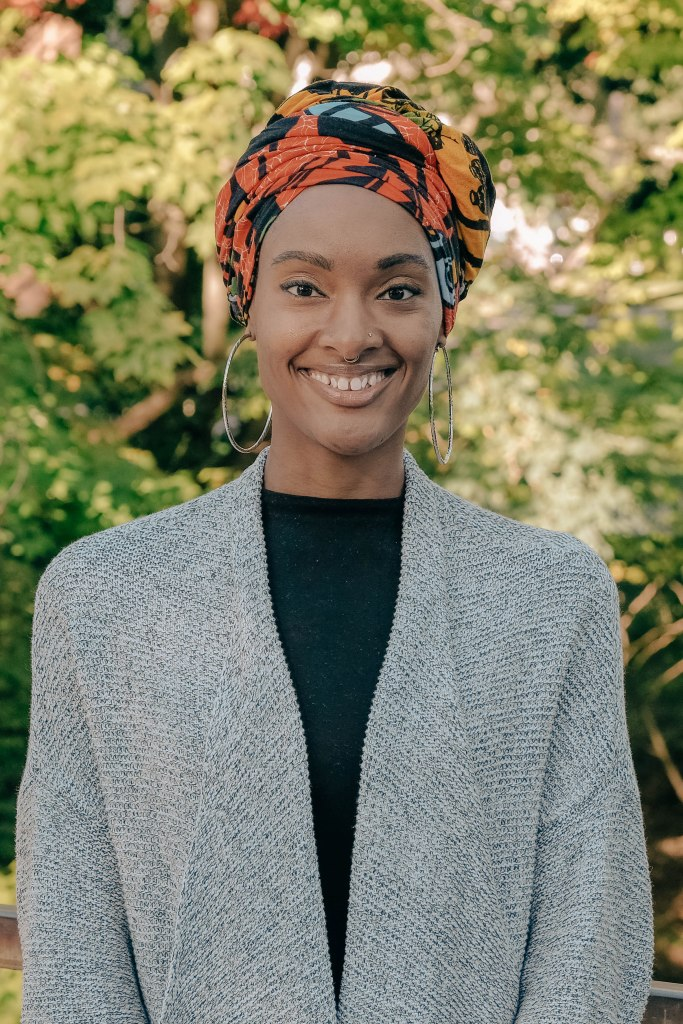 A woman with Black skin stands for a professional photograph. She is wearing a fine gray cardigan over black clothing and an orange, teal, and black headwrap.