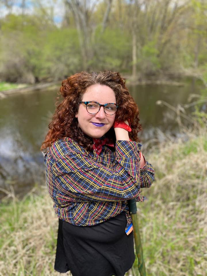 A person with a lot of red, curly hair and white skin is wearing purple lipstick. They are wearing a button up shirt criss-crossed with red, blue, and yellow on a on a starry black background. They lean on a green walking stick.
